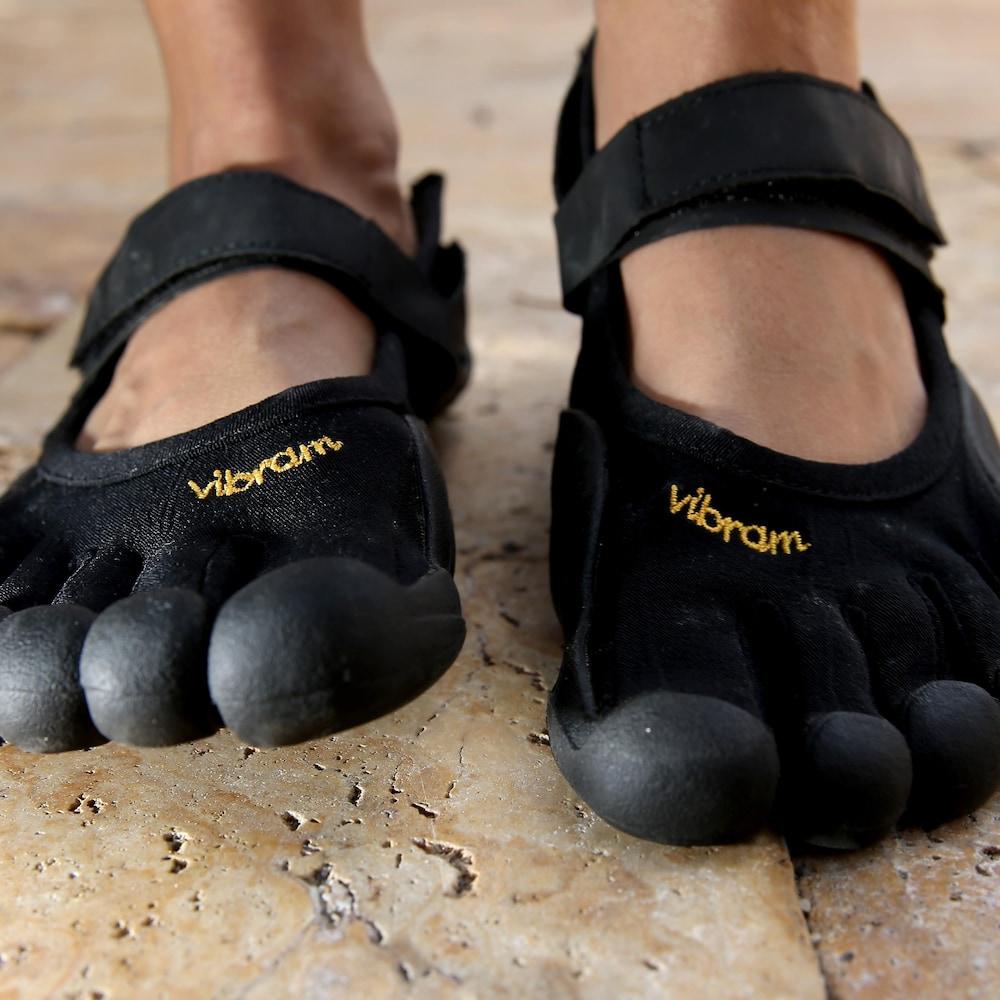 Photo des chaussures à orteil portées par un homme. Chacun des orteils est divisé et la semelle en caoutchouc recouvre le bout de ceux-ci.