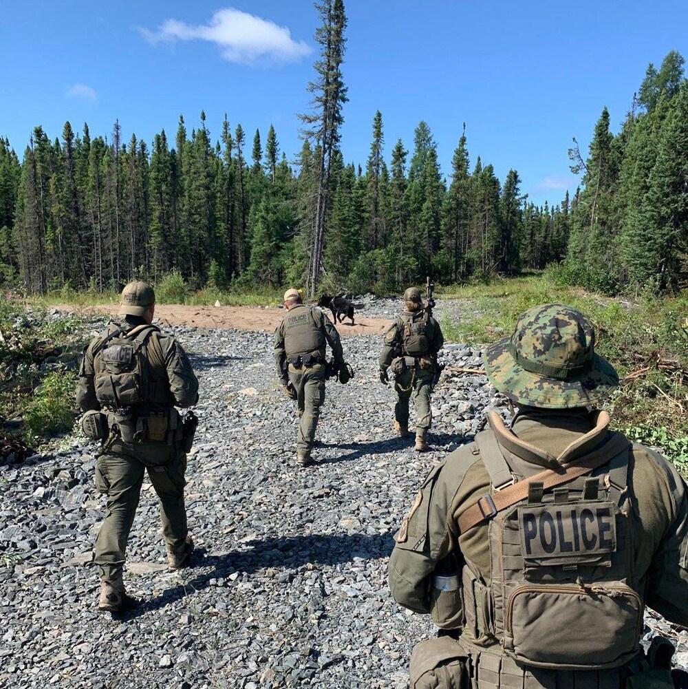 Des policiers en habits militaires marchent.