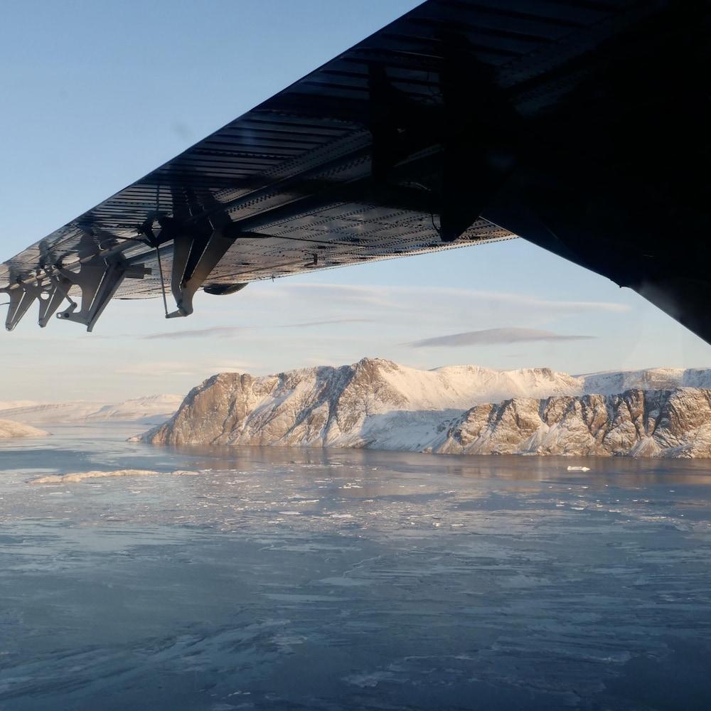 L'aile d'un avion au-dessus d'un paysage d'eau et de glaciers.