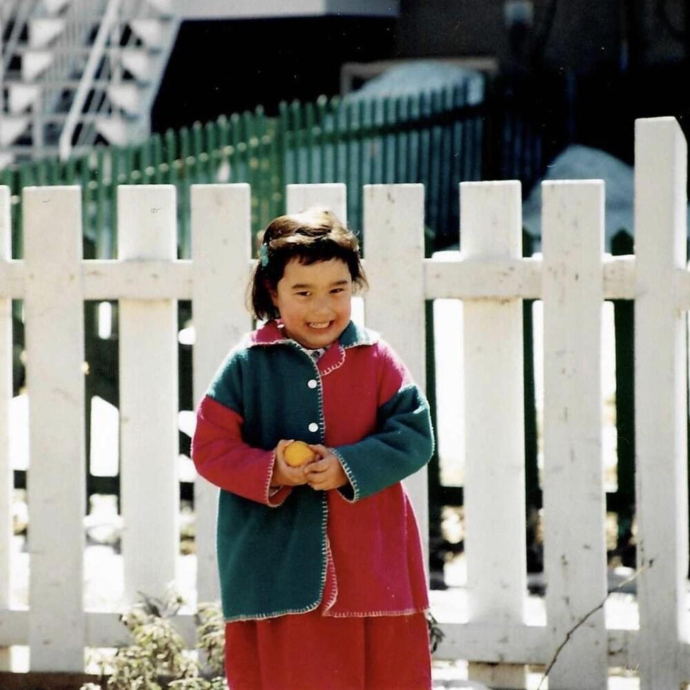 Daphné-Anne Olepika, alors qu'elle était une petite fille, debout devant une clôture.