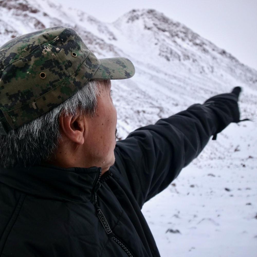 Jimmy Qaapik montre un glacier avec son index, à l'horizon.