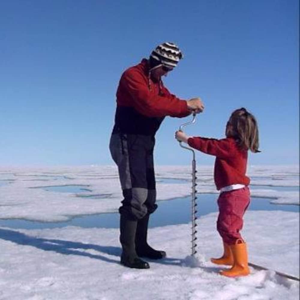 Léonie et son père percent un trou dans la glace avec une foreuse manuelle.