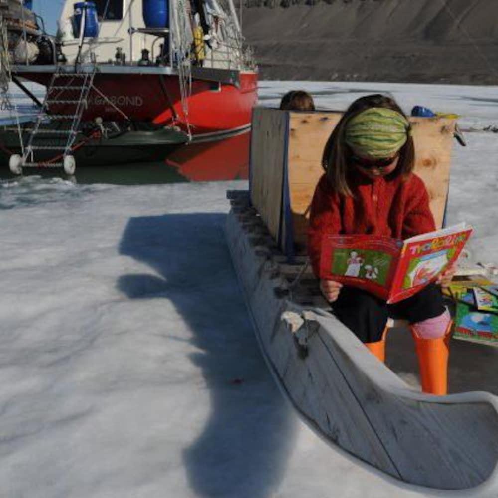 Une fillette lit un magazine assise sur un traîneau près d'un bateau dans un mer glacée.
