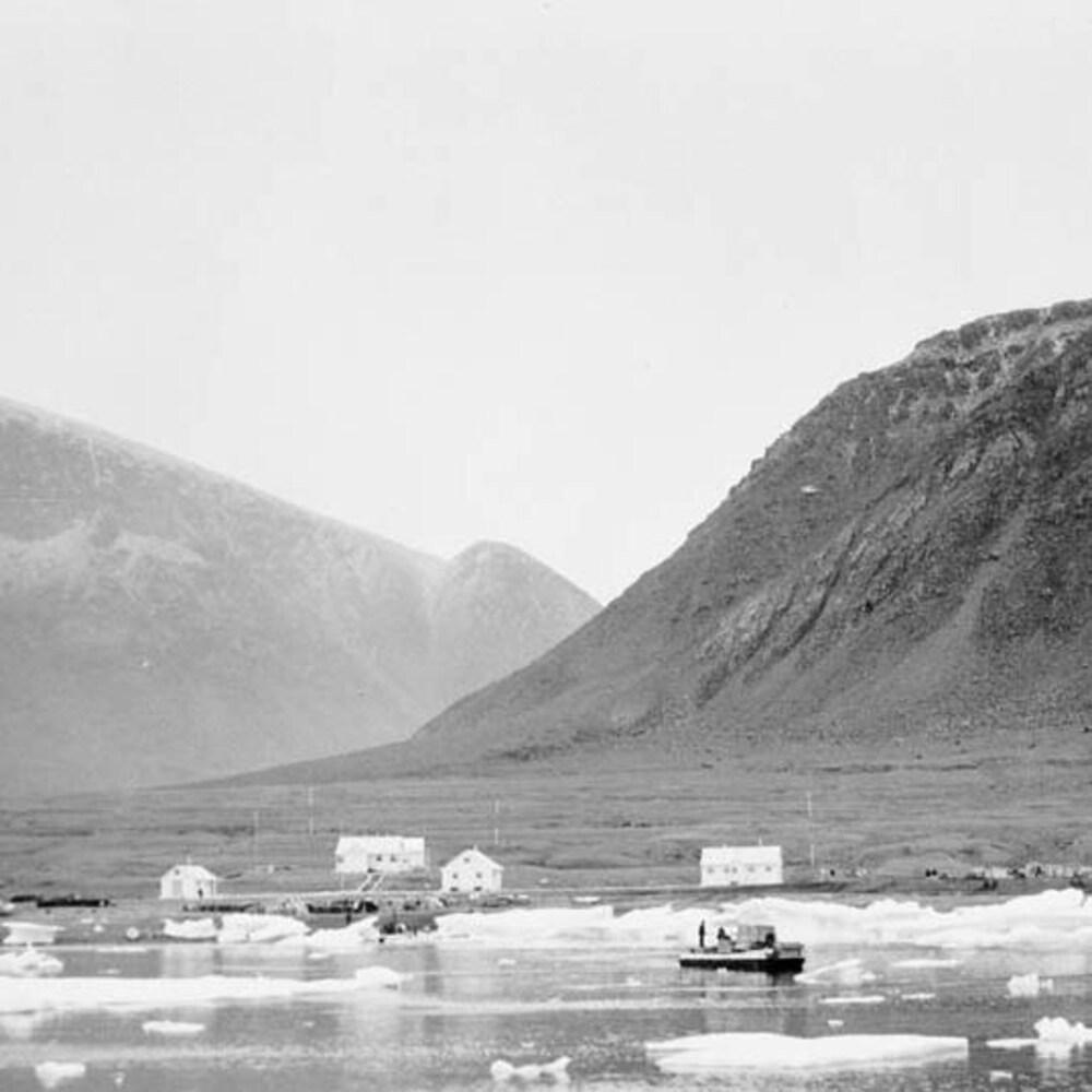 Un ponton sur l'eau où flottent des blocs de glace, près d'une rive avec des habitations.