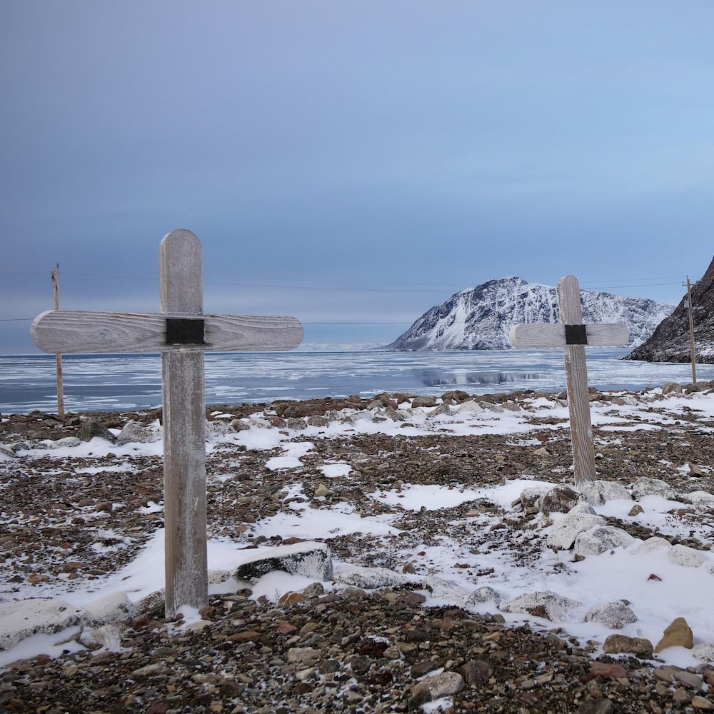 Des croix de bois plantés dans un sol aride et en partie enneigé, près de la rive, dans le cimetière de Grise Fiord.