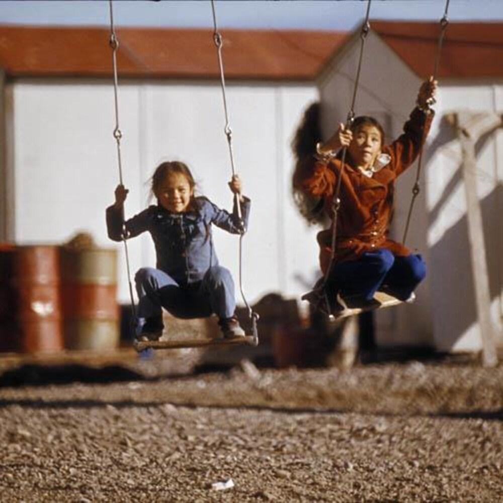 Photo d'archives de deux fillettes accroupies sur des sièges de balançoire.
