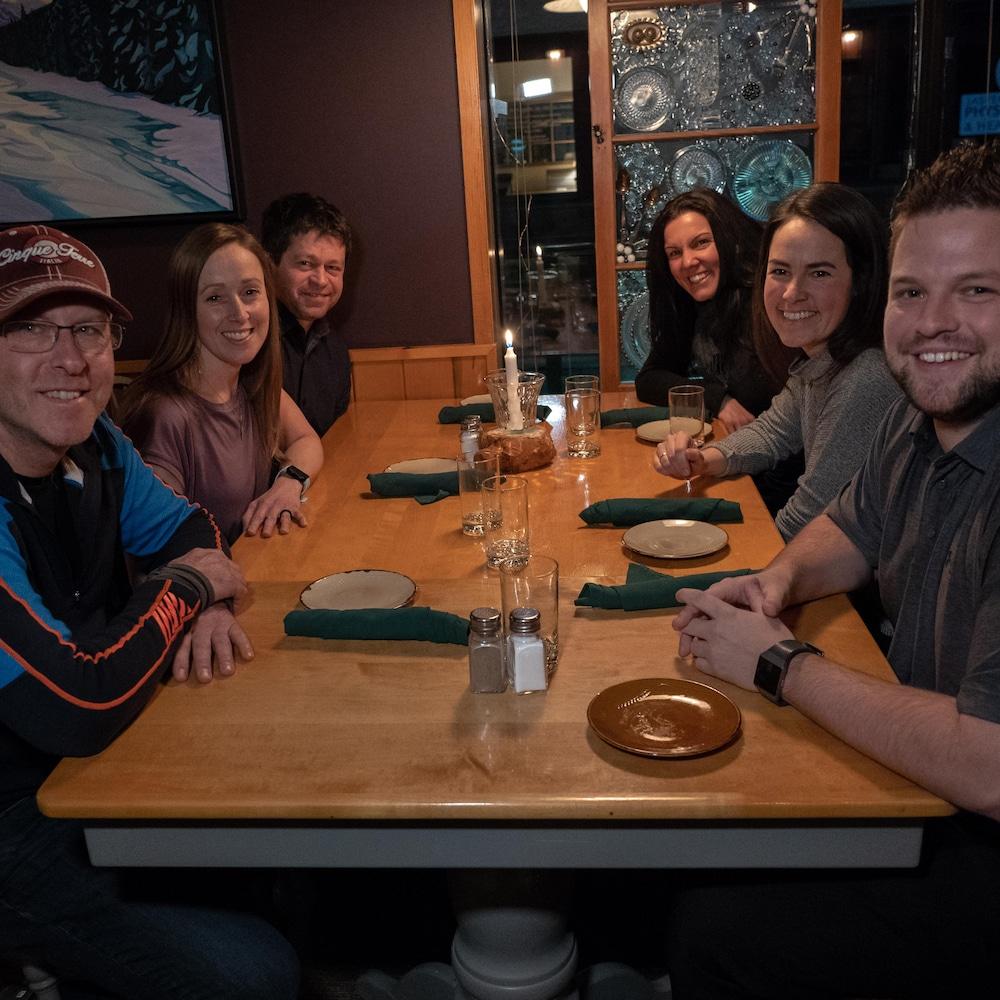 Un groupe de trois hommes et trois femmes tout sourire sont assis à une table et regardent la caméra.