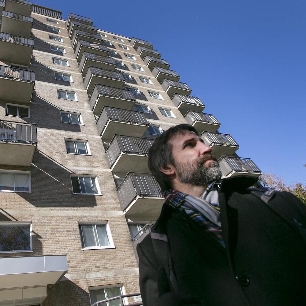 Steven Guilbeault devant un immeuble résidentiel à Montréal.