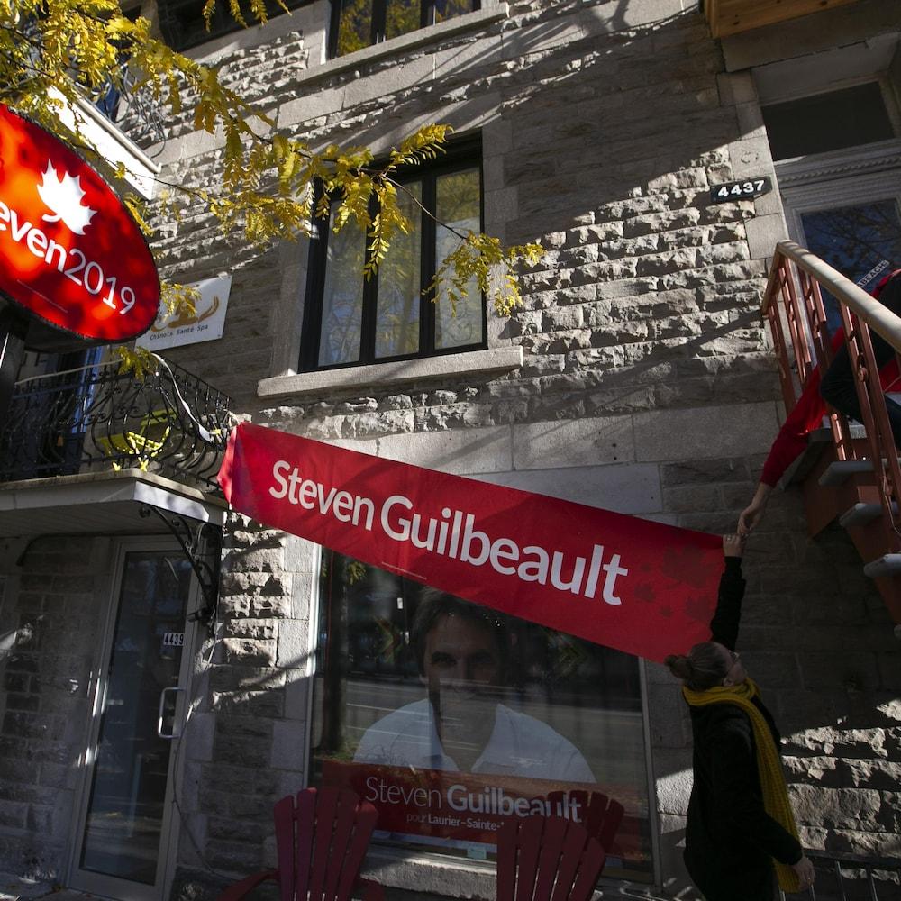 Des employés installent une bannière avant un point de presse sur la rue St-Denis.