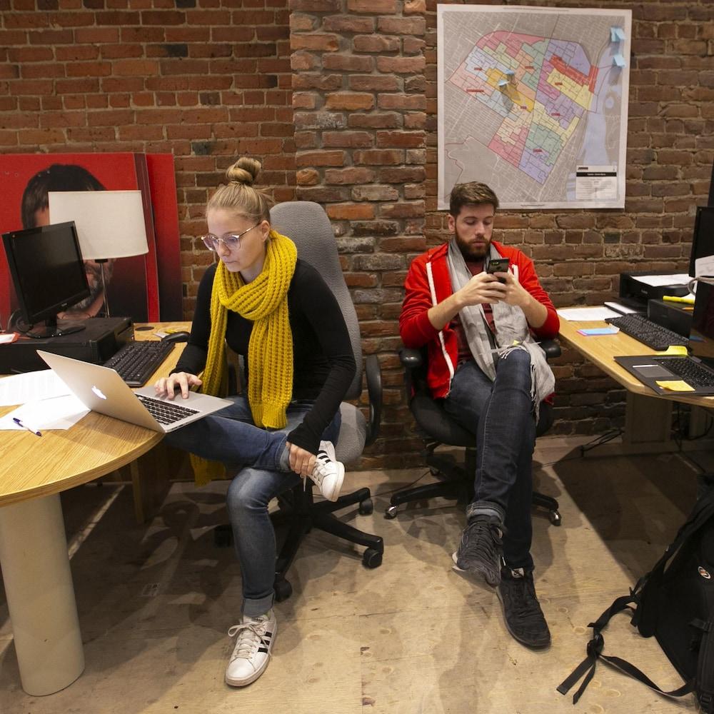Deux conseillers de Steven Guilbeault, une femme et un homme, assis derrière des bureaux dans son local de campagne.