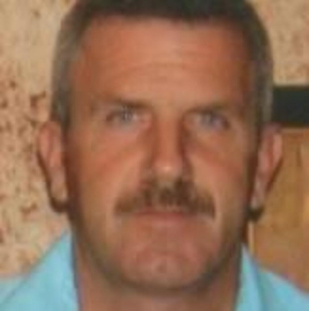 Photographie d'un homme aux cheveux courts et portant une moustache fine
