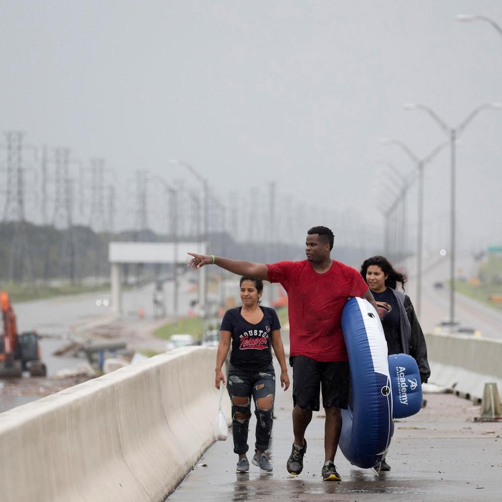Trois personnes marchent sur une autoroute inondée, au Texas.