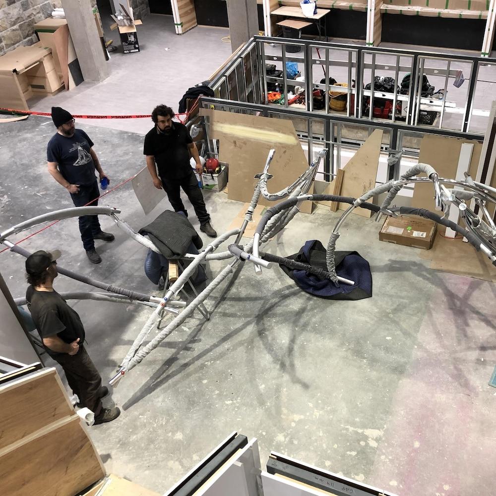 Une grande structure métallique au sol, trois travailleurs à proximité.