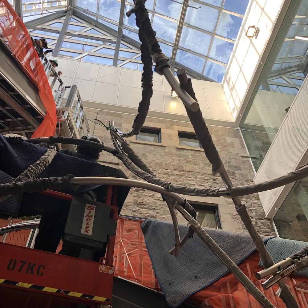 La sculpture métallique en suspension au-dessus de l'escalier, sous le toit vitré à travers lequel perce le ciel bleu.