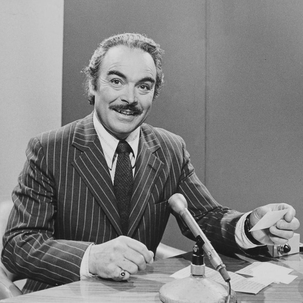 Henri Bergeron, carton à la main, animant assis à un bureau devant un micro sur pied.