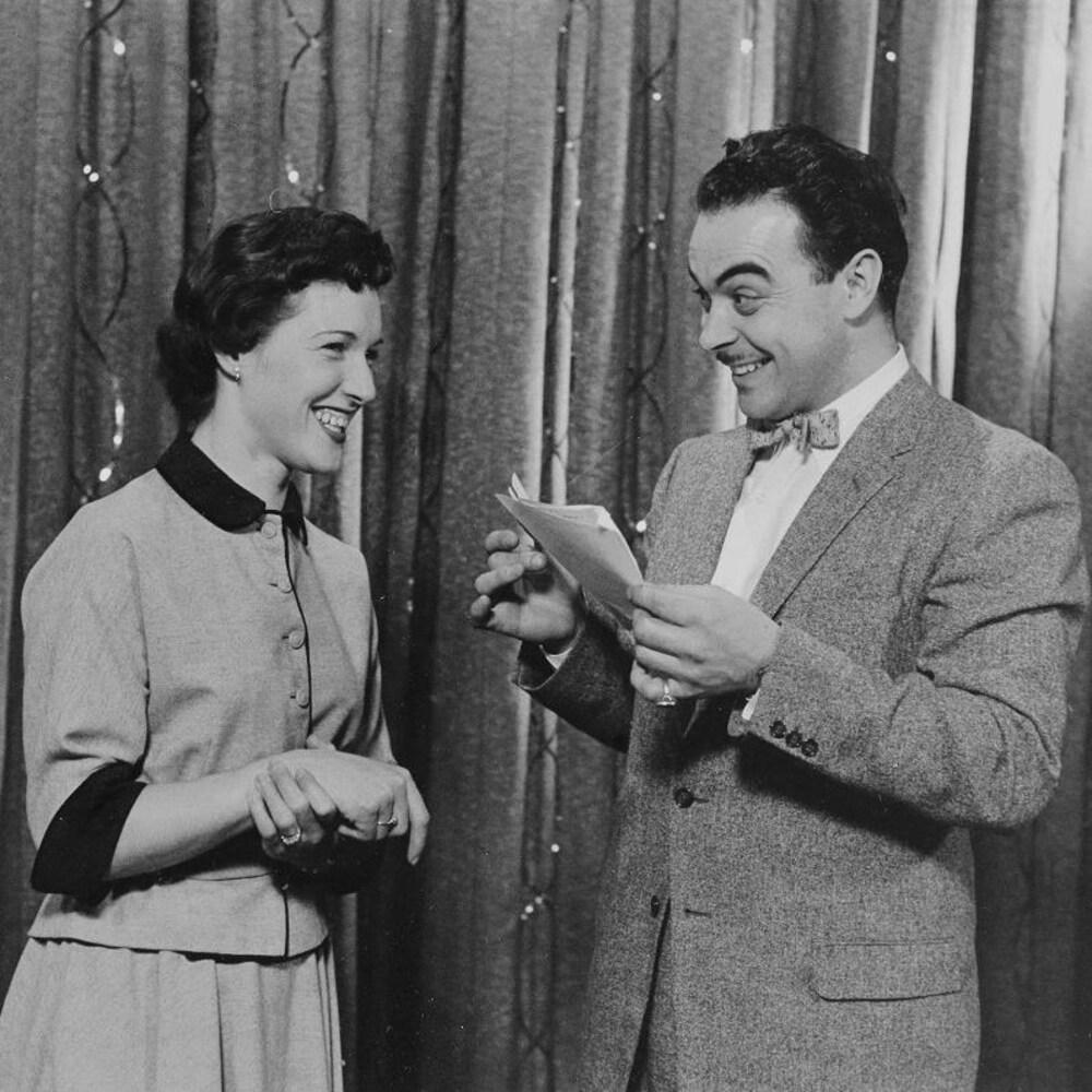 Sur une scène, Henri Bergeron, feuilles à la main, regarde une concurrente en souriant.