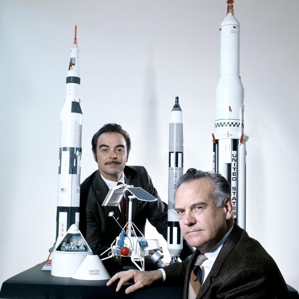 L'animateur Henri Bergeron et le professeur Marcel Sicotte devant des maquettes de fusées.