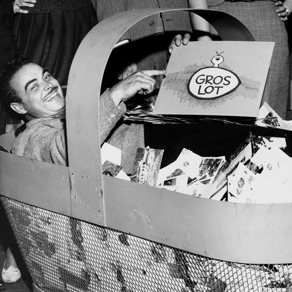 L'annonceur Henri Bergeron assis dans un panier géant contenant le courrier des téléspectateurs.