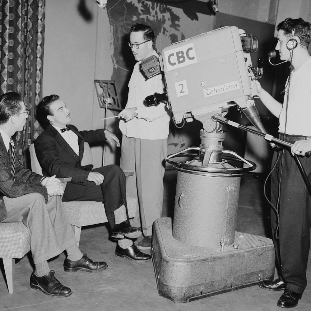 Henri Bergeron, assis devant la caméra aux côtés de l'animateur Bruce Marsh, conversant avec l'équipe de production.