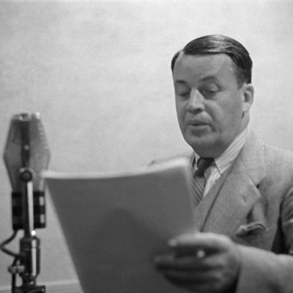 Dans un studio de radio, le comédien Albert Duquesne interprétant le rôle d'Alexis Labranche, lit son texte derrière un micro.