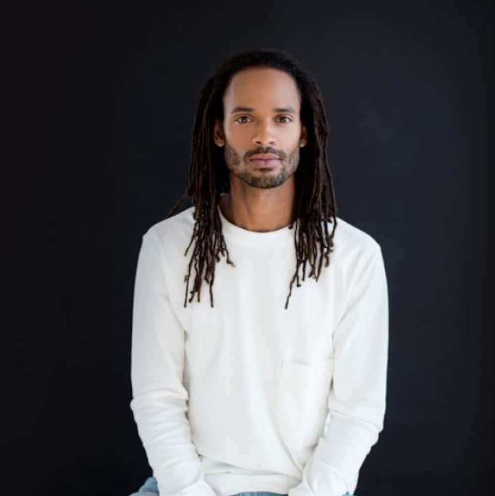 Un homme noir avec un chandail blanc, les cheveux tressés, est assis sur un banc devant un fond noir. Il regarde vers la caméra.