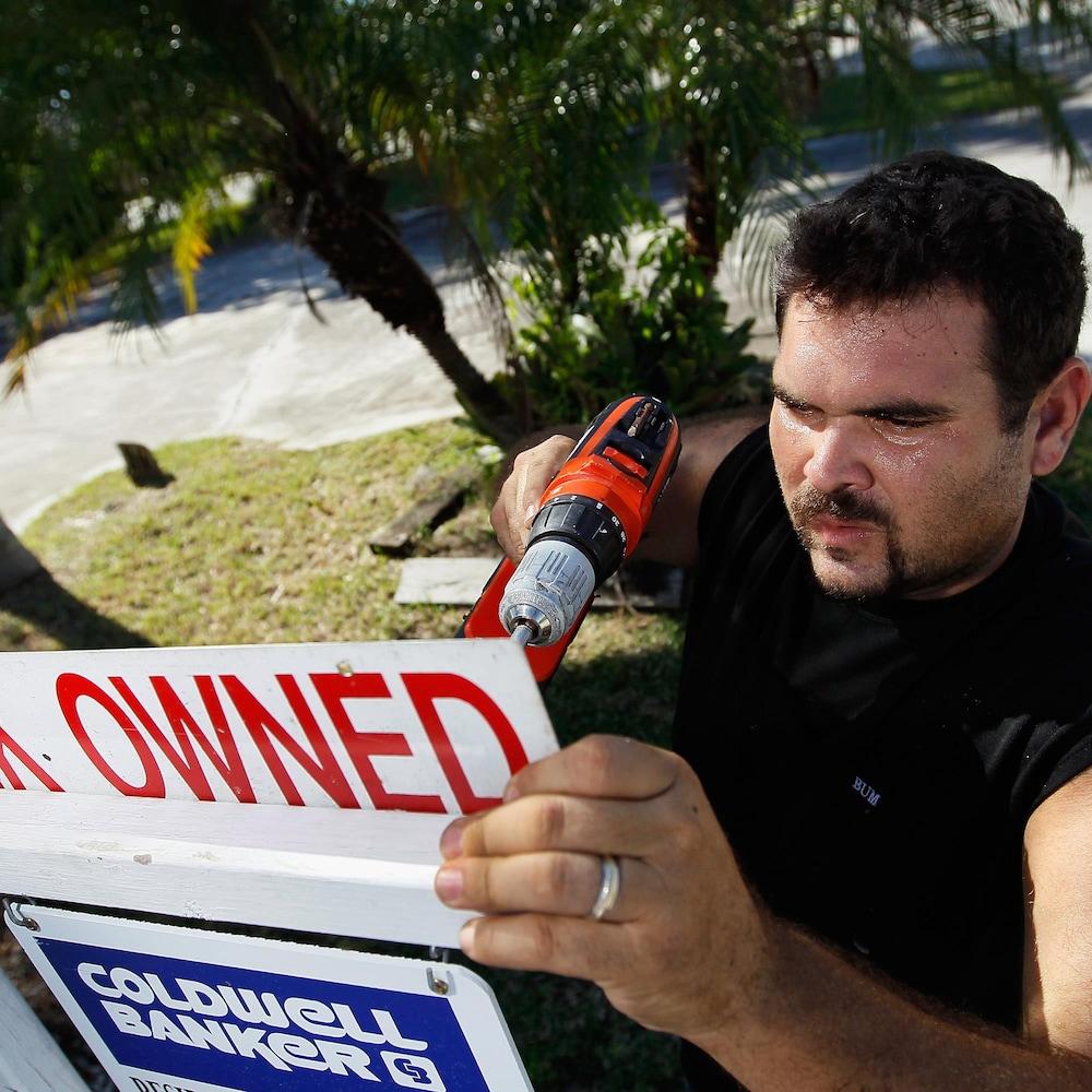 Un homme procède à l'installation d'une affiche indiquant qu'une propriété est en reprise de finance.