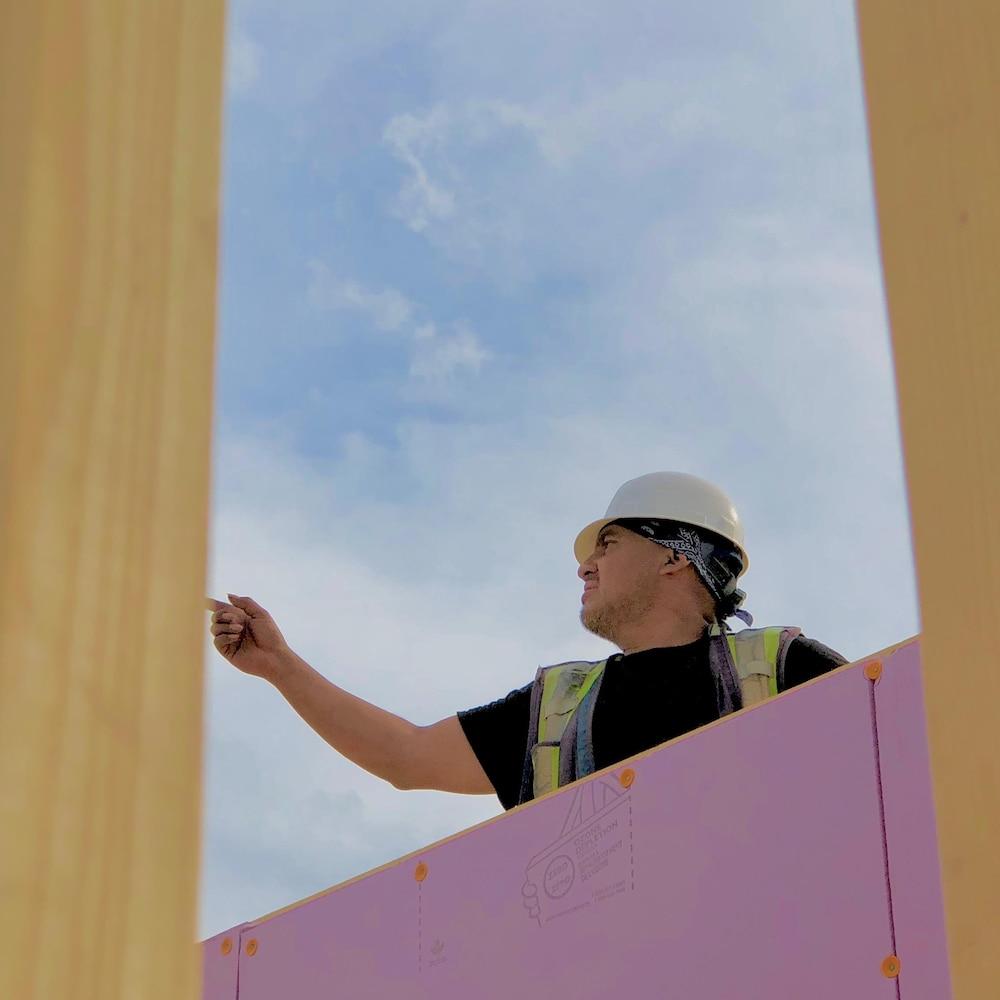 Carlos Espen est debout sur la charpente d'une maison