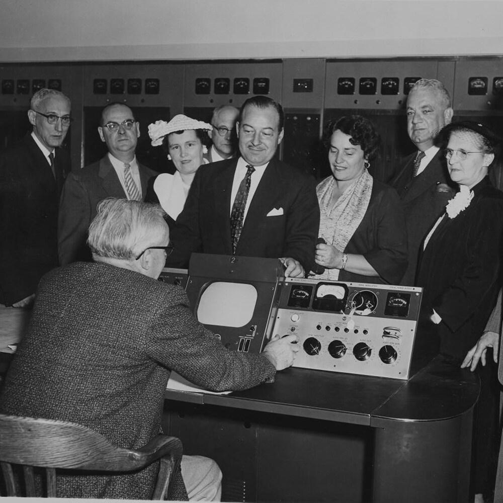 Un groupe de dignitaires se tient devant le comptoir de la régie avec un technicien au travail devant des moniteurs et autres équipements.