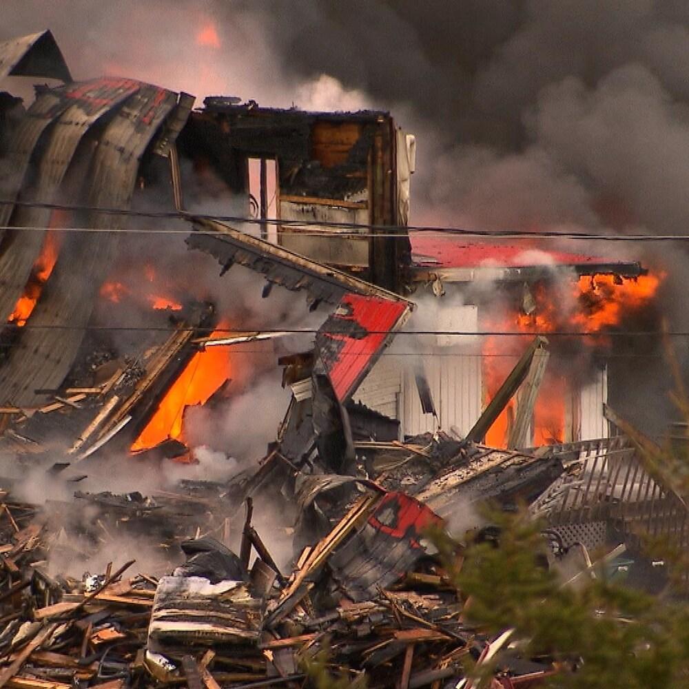 Tas de ruines avec des flammes et de la fumée épaisse.
