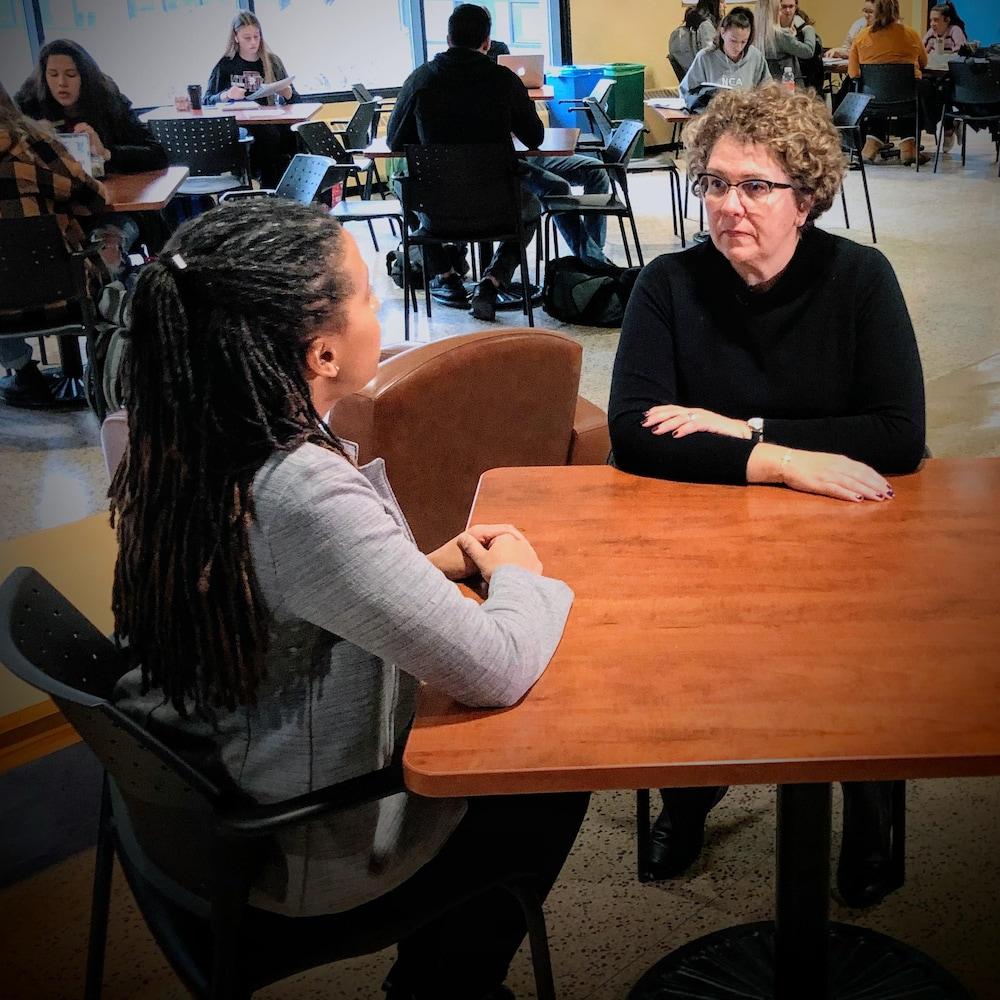 Deux femmes discutent à une table dans une salle à manger.