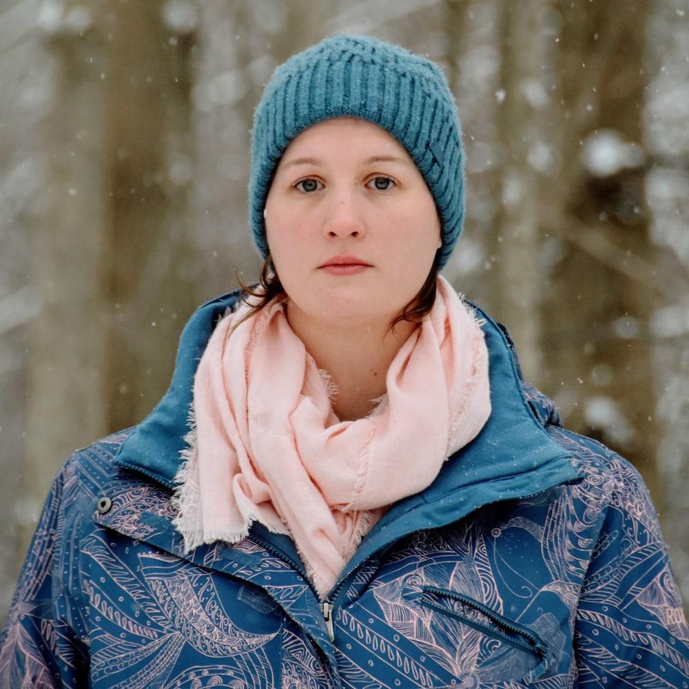 Un femme près d'un bois alors qu'il neige.
