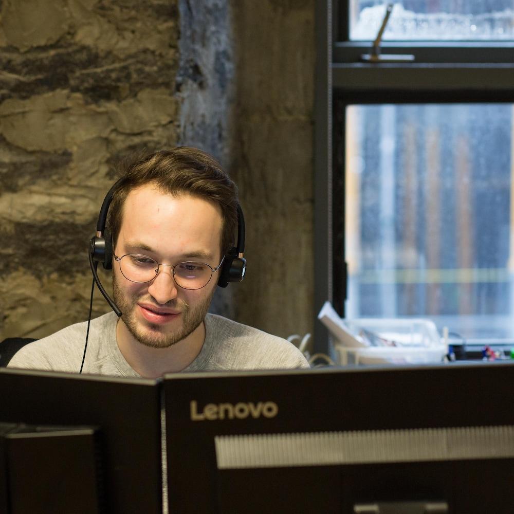Un jeune homme, avec des lunettes rondes et un casque d'écoute, regarde ses écrans d'ordinateur.
