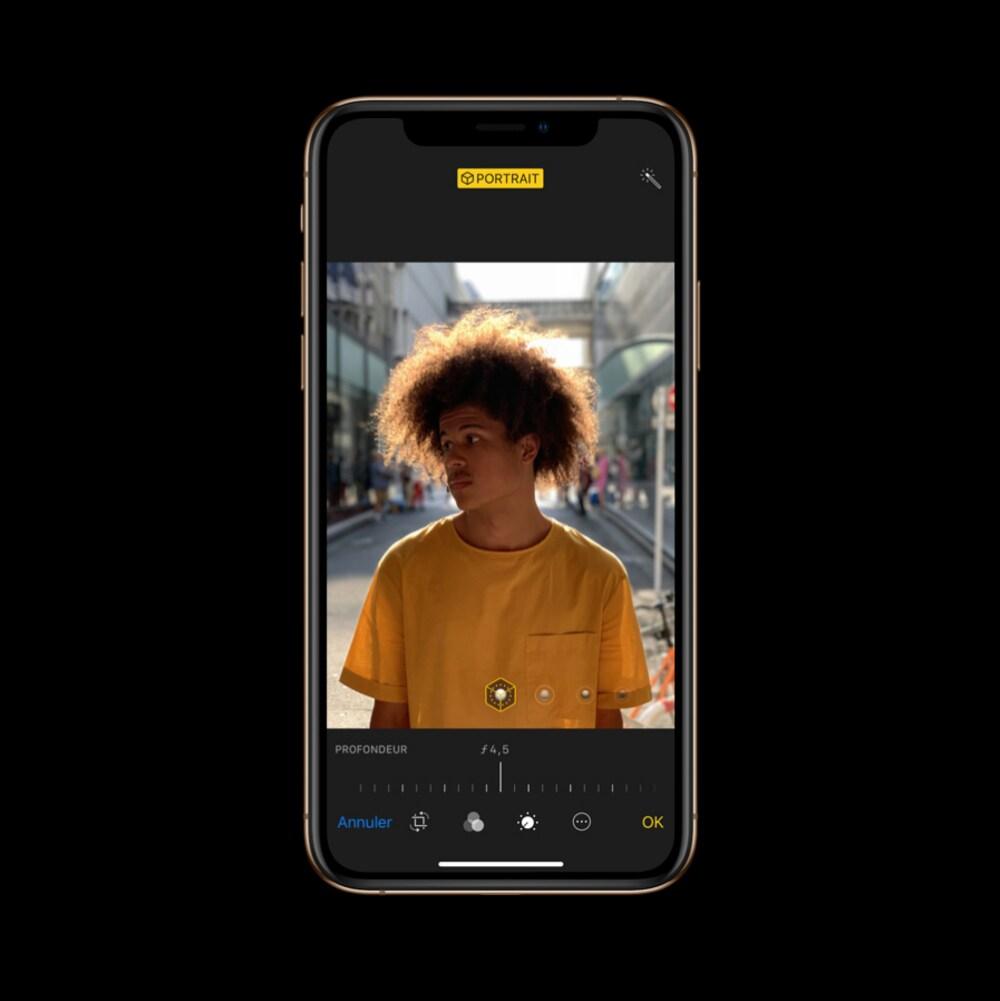 Une photo montrant un iPhone Xs sur lequel est affichée la photo d'un homme de race noire aux cheveux frisés ébouriffés qui porte un t-shirt jaune.