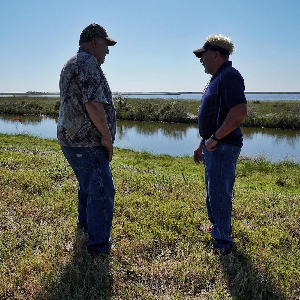 Wenceslas Billiot fils et Robert Billiot se tiennent debout dans un champ.