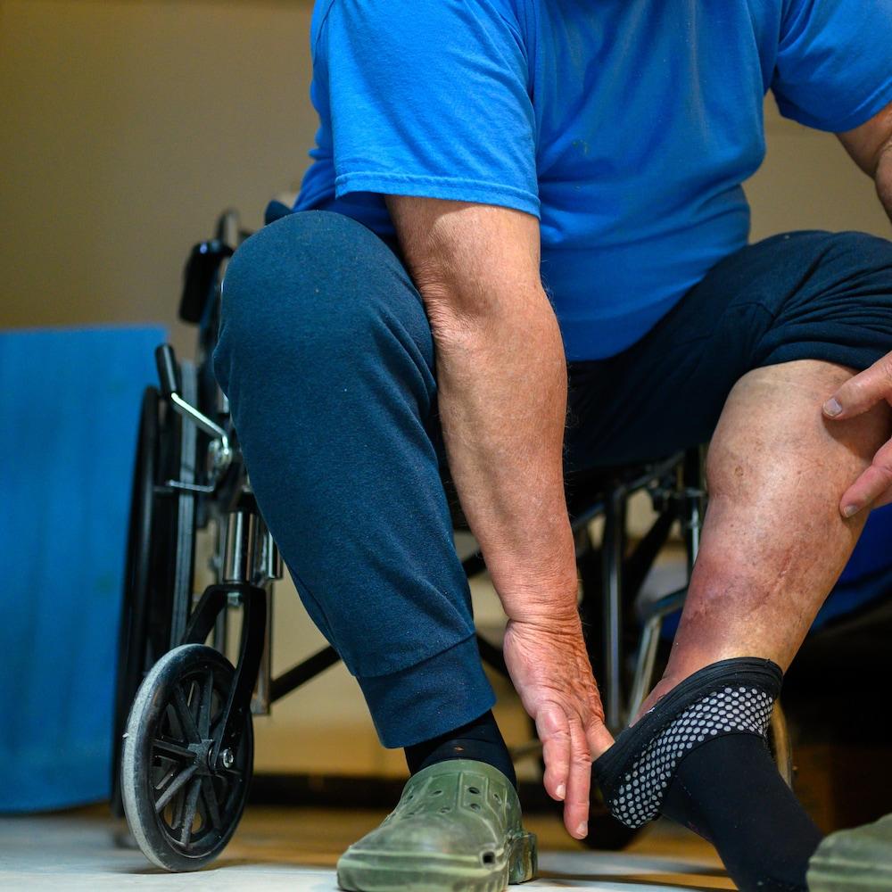 Un détenu âgé de plus de 80 ans en perte d'autonomie montre une de ses jambes.