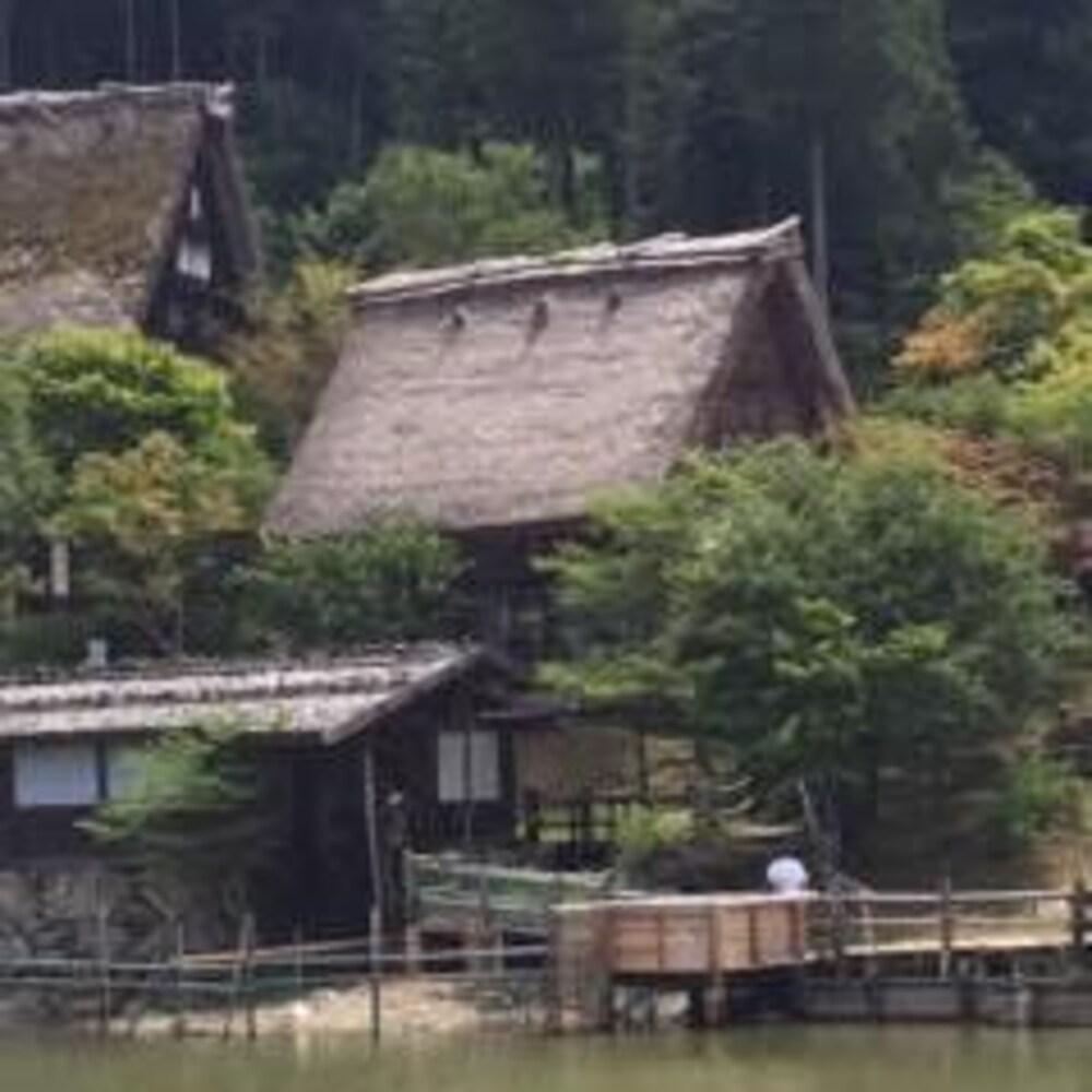 De vieilles maisons dans une montagne entourées de verdures, avec un plan d'eau au premier plan.