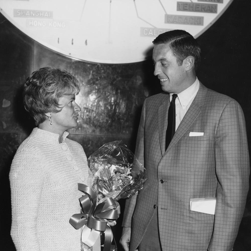 Jean Béliveau regarde  son épouse Élise Béliveau qui tient un bouquet de fleurs.