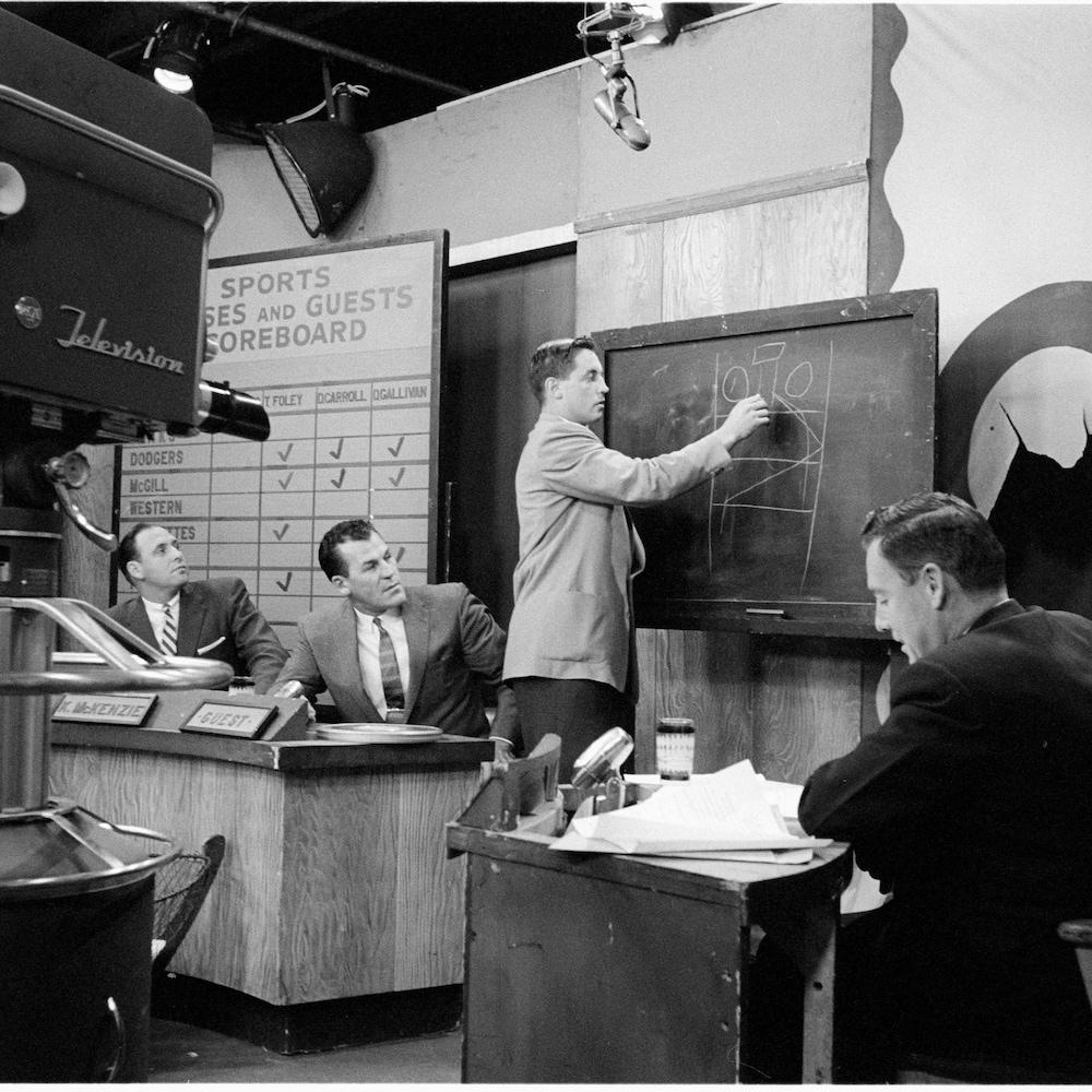Jean Beliveau en studio qui dessine à la craie sur un tableau noir, des analystes sportifs et animateurs le regardent.