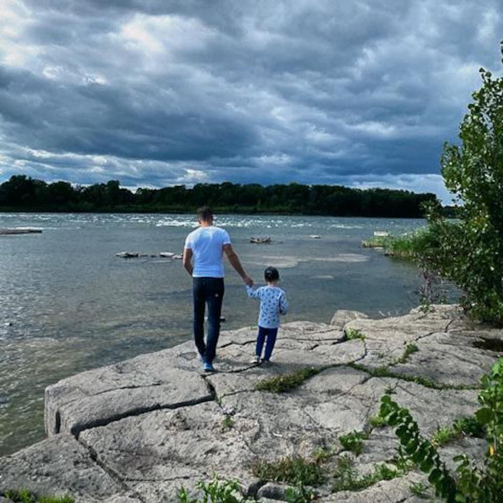 Jean-Luc Brassard et son fils Grey marchent sur des rochers en bordure de l'eau.