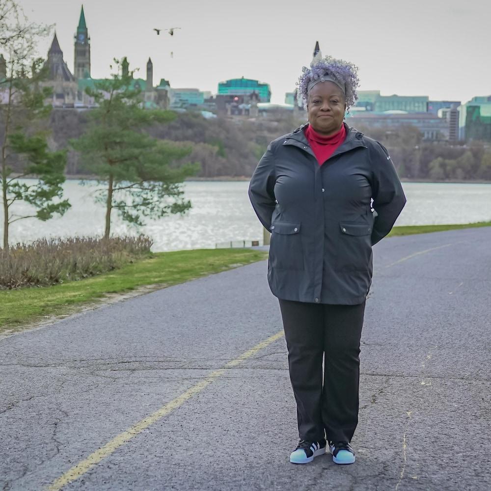 Jennie Esnard sur la piste cyclable en bordure de la rivière des Outaouais et du parlement canadien.