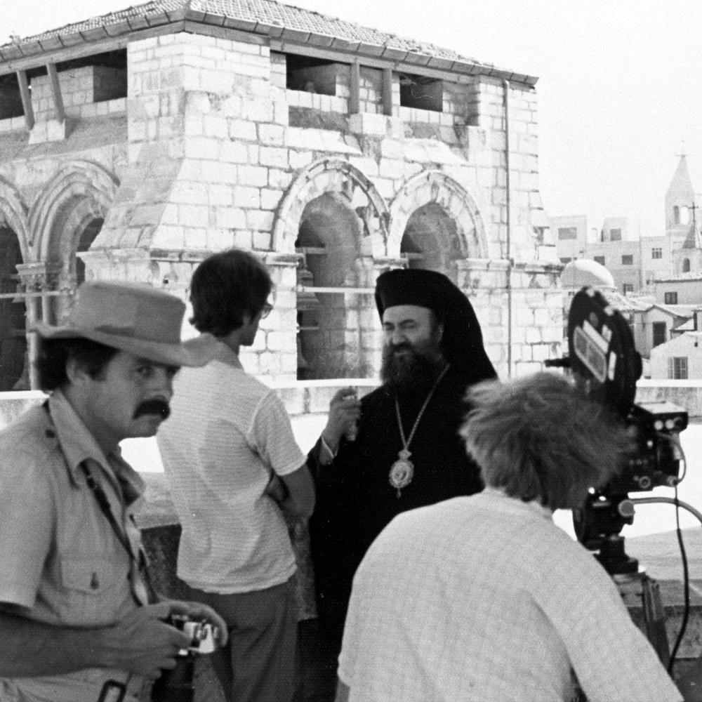 Un photographe et un caméraman devant le père Yvon Hubert qui s'entretient avec un archevêque grec orthodoxe. Édifices en arrière-plan.
