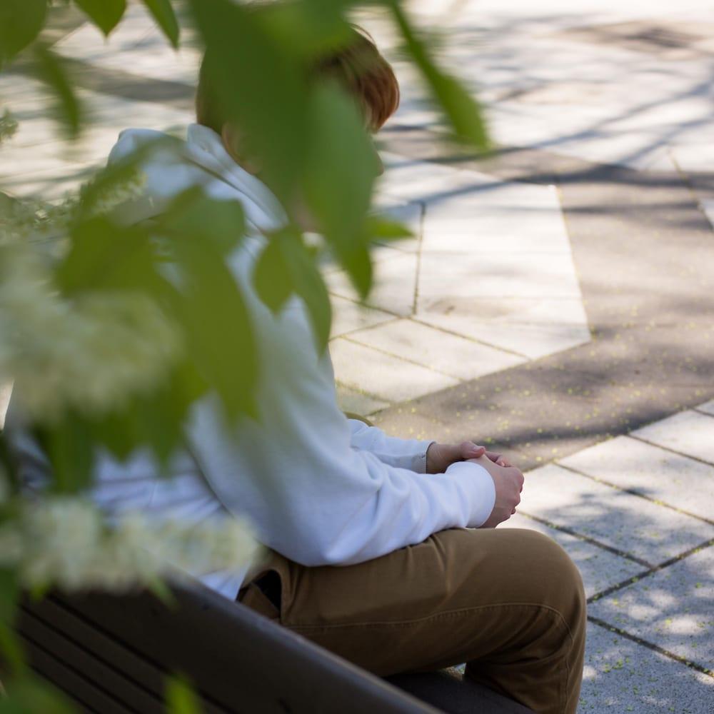 Alessandro est assis sur un banc de parc, son visage camouflé par du feuillage.