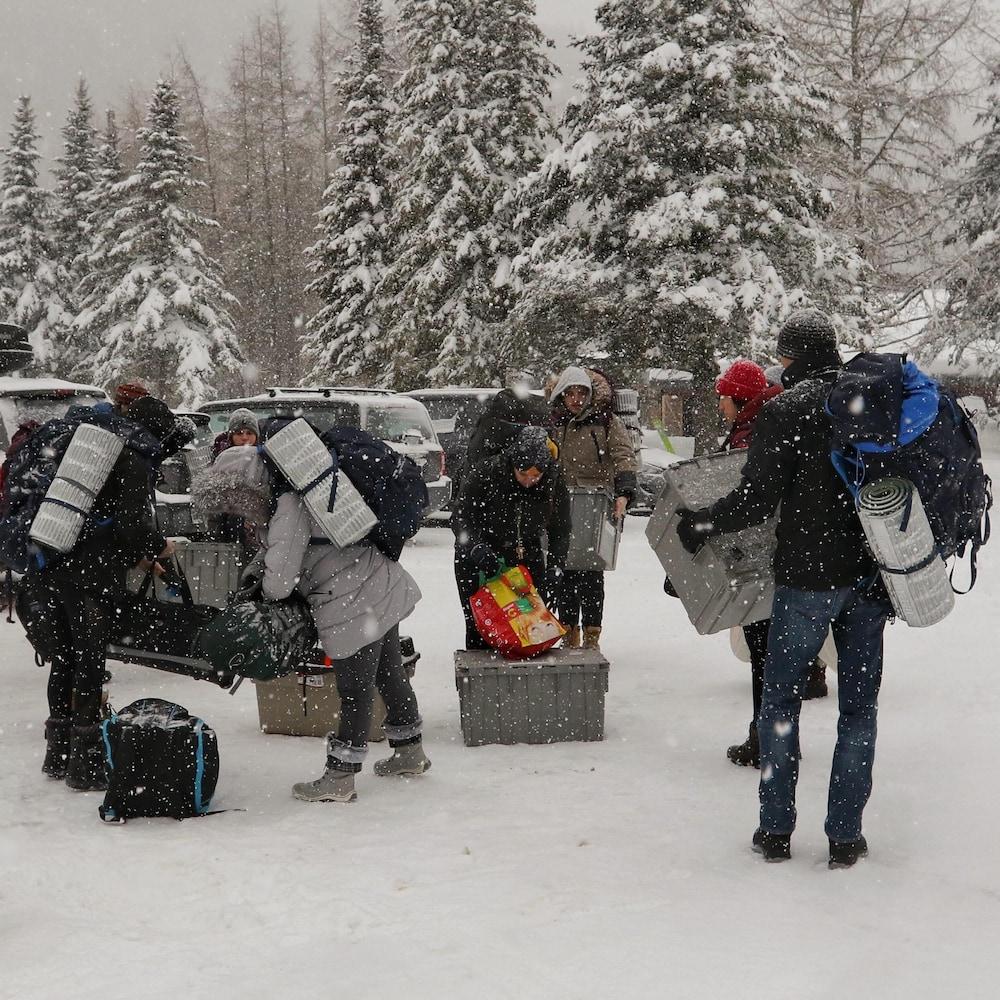 Des jeunes transportent des sacs dos et des boîtes de plastique. Un paysage hivernale les entoure.