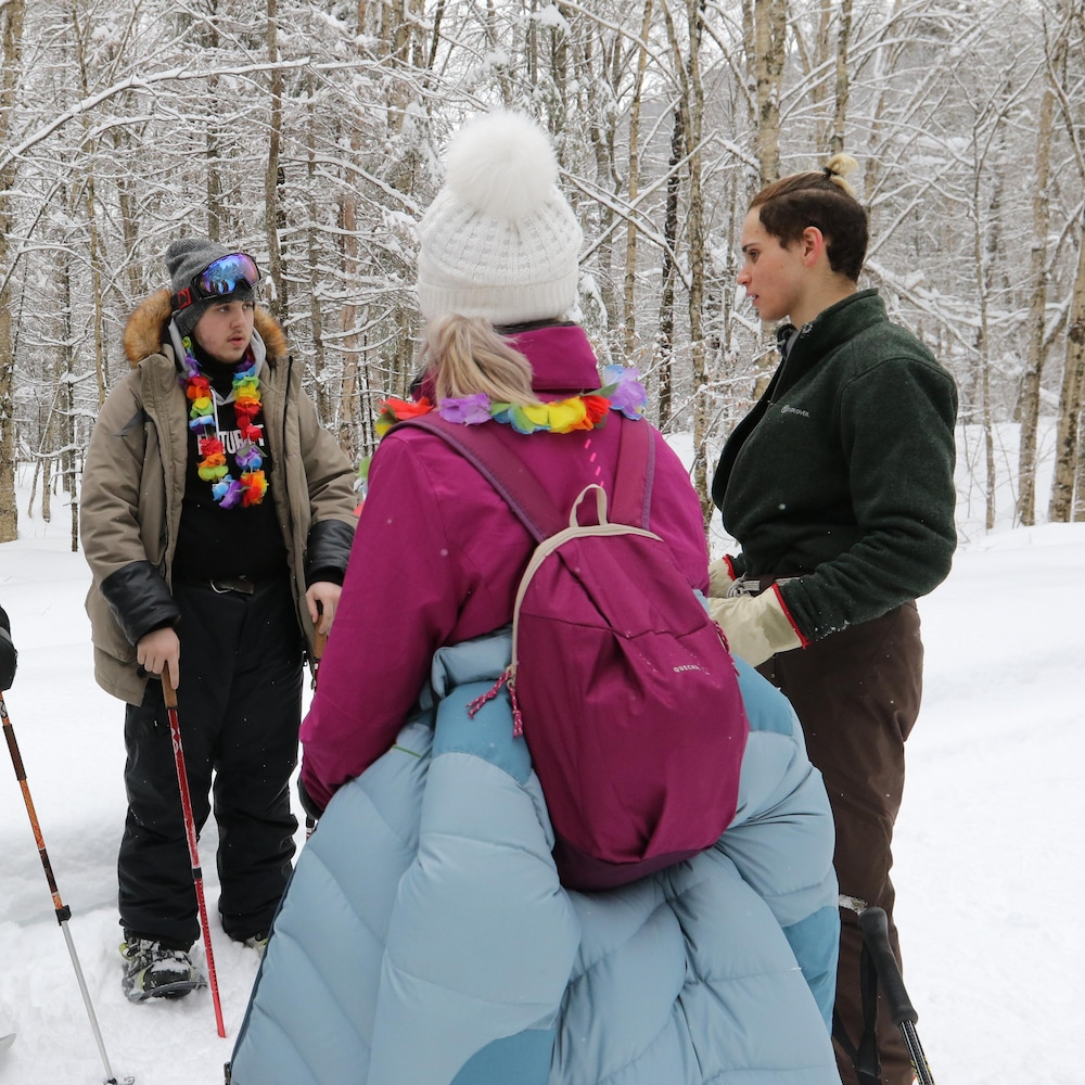 Les jeunes forment un cercle et discutent dans un sentier enneigé.