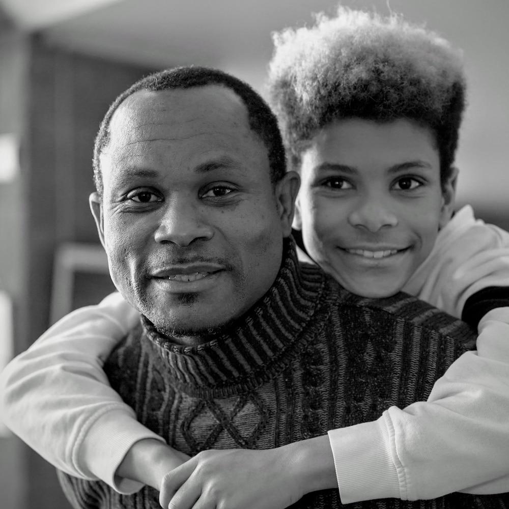 TJ Boussombo se tient sur les épaules de son père.