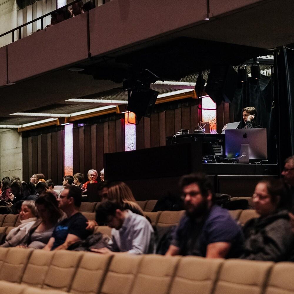Maxime Goulet est derrière plusieurs ordinateurs dans le fond de la salle de spectacle. Quelques spectateurs attendent le début de la représentation.