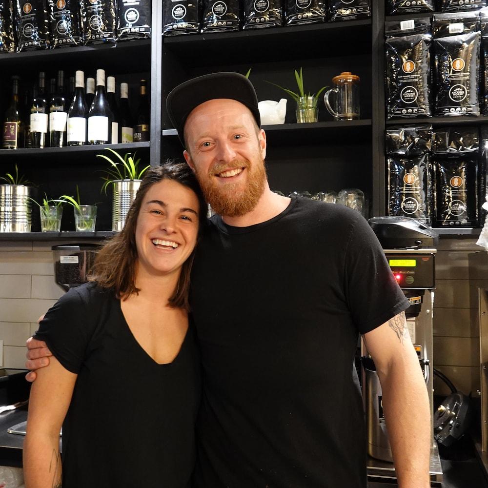 Un jeune couple composé d'un homme et une femme dans la jeune trentaine posent devant des étagères avec des sacs de café et des bouteilles de vin.