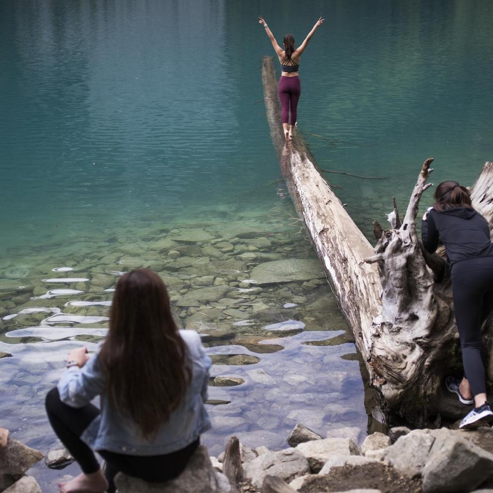 Une jeune femme fait une pose gracieuse sur un tronc à demi-submergé aux abords d'un lac du parc britanno-colombien de Joffre Lakes.