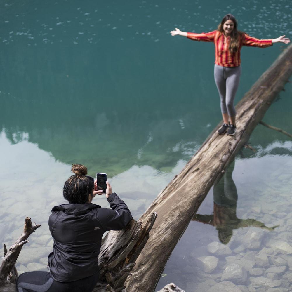 Une jeune femme prend son amie en photo sur un tronc à demi-submergé aux abords d'un lac du parc britanno-colombien de Joffre Lakes.
