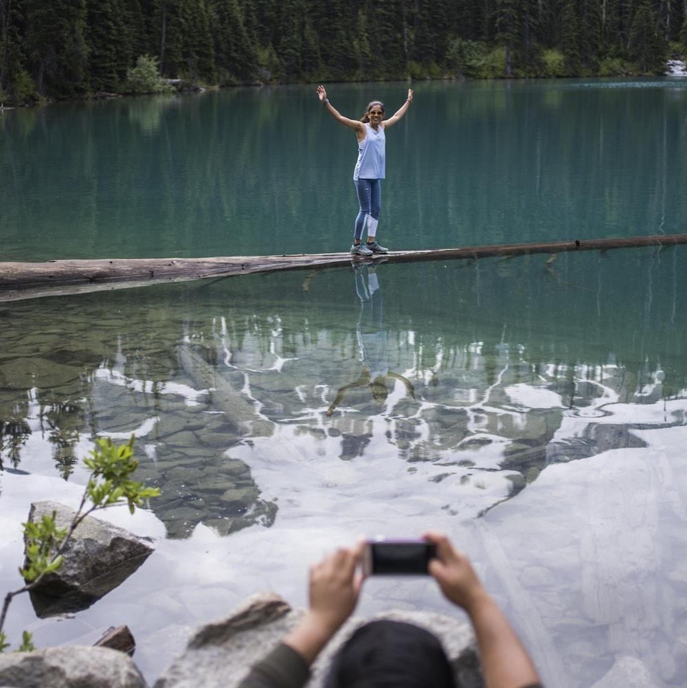 Une jeune femme se fait prendre en photo sur un tronc à demi-submergé aux abords d'un lac du parc britanno-colombien de Joffre Lakes.